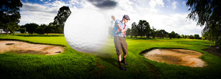 golf man: Sport Panorama Of A Vintage Golfer Hitting A Flying Golf Ball Mid Air On A Golfing Green In A Depiction Of Speed And Top Flight Stock Photo