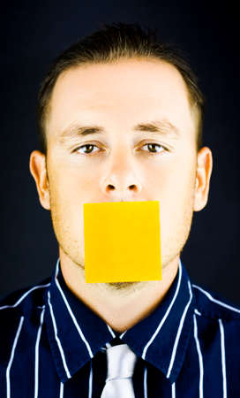 stuck up: Close up shot on the face of a business man with blank, yellow paper note over his mouth on black background Stock Photo