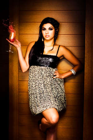 unsettled: Picture Of Glamour And Poise With A Beautiful Young Woman Standing In Front Of Nightclub Wall Holding A Glass Of Unsettled Wine While Splashing Out On The Town Stock Photo