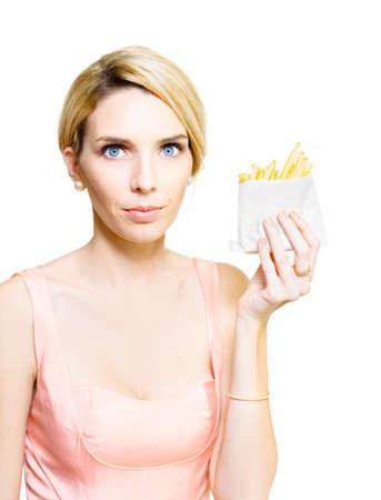 grasas saturadas: Mujer que soporta una comida para llevar que sirve de un paquete de grasa de las patatas fritas fritas empapadas en aceite de engorde saturadas en una dieta y la comida chatarra concepto poco saludable