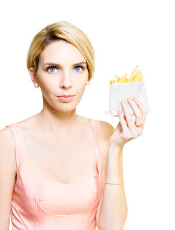 high calorie foods: Woman holding up a takeaway serving of a greasy packet of deep-fried potato chips soaked in fattening saturated oil in an unhealthy diet and junk food concept