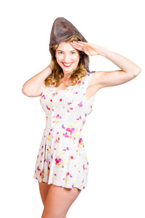 affirmative: Isolated portrait of a pretty female pinup pilot smiling in white floral retro dress gesturing affirmative in aviator cap