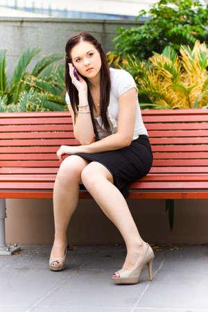 conversaciones: Estilo Joven mujer de negocios Lluvia de un grupo de discusión sobre el teléfono móvil o celular durante una teleconferencia de llamadas mientras está sentado en un banco del parque al aire libre Foto de archivo