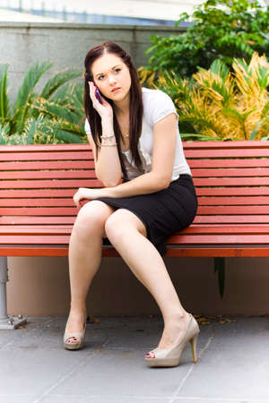 women sitting: Young Stylish Business Woman Brainstorming A Group Discussion On A Mobile Or Cell Phone During A Teleconference Call While Seated On A Park Bench Outdoors Stock Photo