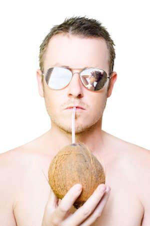 gafas de sol: hombre guapo verano beber un cóctel de coco mientras se ve una mujer hermosa morena se relaja contra una palmera en un concepto de vacaciones paraíso y el turismo