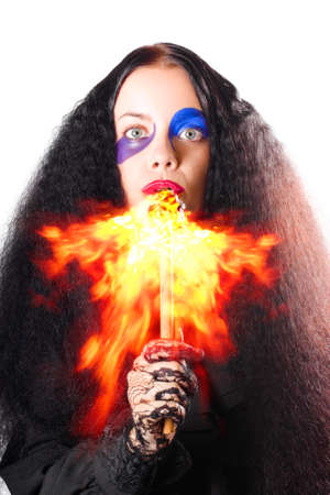 Scary woman with long black hair breathing or blowing fire from mouth, white background