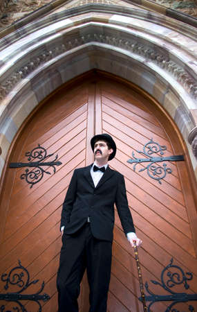 dapper: Well Dressed Man Stands By A Closed Church Door Early For Sunday Mass Stock Photo