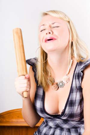 busty: El ama de casa infeliz llanto en la cocina con la revista Rolling Pin roto en una representación de un error de cocina Foto de archivo