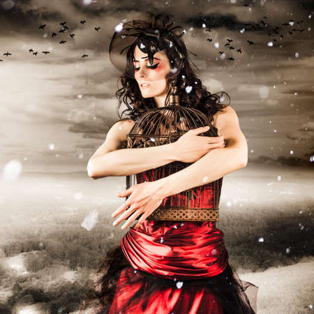 grasp: Fashion Portrait Of A Romantic Woman Feeling The Cold Grasp Of Winter When Releasing Her Love To Freedom From A Snow Capped Romance Stock Photo