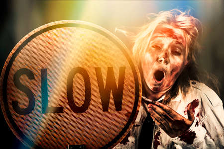 slow: Yawning zombie business person holding slow sign down traffic sign. Business hardship metaphor
