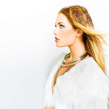 sexy angel: Profile shot of woman wearing big gold necklaces and white feather top looking to copyspace in a hair makeup and fashion concept