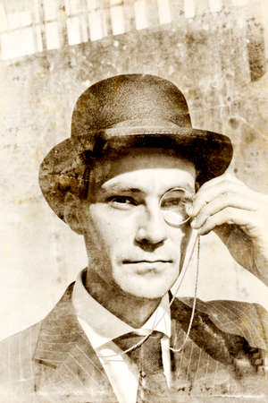 austere: Grunge Sepia Photograph On The Head Of A Old Fashioned Man Wearing Bowler Hat And Holding Monocle In a Vision Of History Conceptual