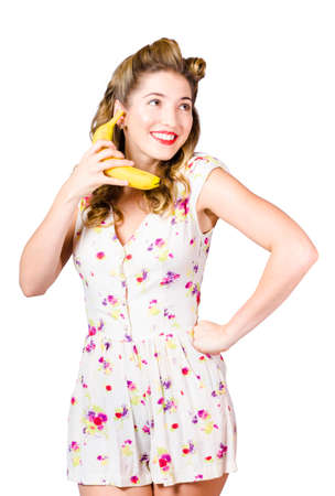 imaginary dialogue: Comical photo of a happy retro pin up girl in old-fashion attire going bananas when chatting on fruit telephone. Fruity gossip Stock Photo
