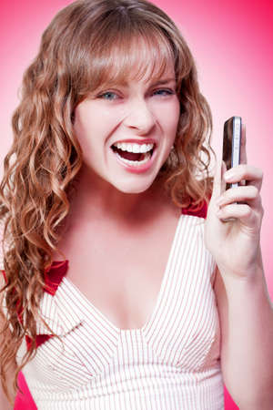 tantrum: Business woman throwing a temper tantrum as she expresses her displeasure with news that she has just received over her mobile phone on a pink studio background