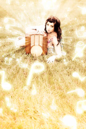 transcend: Musical Communication Concept With Music Melody Notes Transcending Out Of A Old Wireless Radio Held By A Woman In A Field During A Vintage Frequency Broadcast Stock Photo