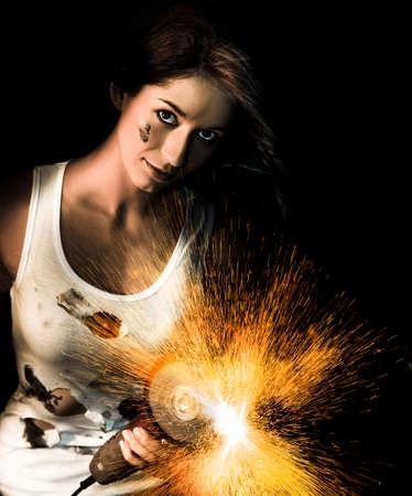 molinillo: Oscuro retrato de un artesano de sexo femenino creando una lluvia de chispas de fuego con su amoladora angular de mano Foto de archivo
