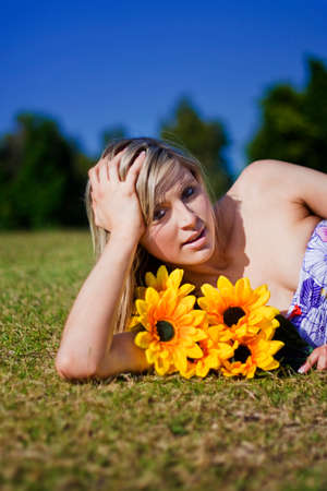 lays: Summer Sun Flowers Woman Lays With Bright Yellow Sunflowers In Her Arms In Summers Sunny Sunshine During Sunlight