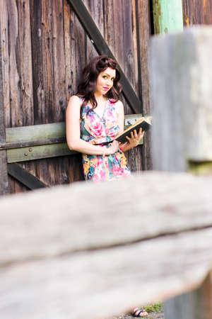 stillness: Woman On A Outback Country Vacation Getaway Leans Against A Farm Shed With A Book To Enjoy The Serene Still Silence And Stillness Of A Relaxing Reading Activity Stock Photo