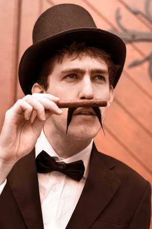 bygone: Portrait Of A Young Gentleman In A Black Suit And Top Hat Smelling Or Sniffing A Cigar While Reminiscing About The Bygone Days