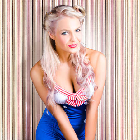 pin stripe: Beautiful Cheeky Blond Woman With Fifties Hairstyle Dressed As A Classic Pinup Model In Cute Sailor Outfit Stock Photo