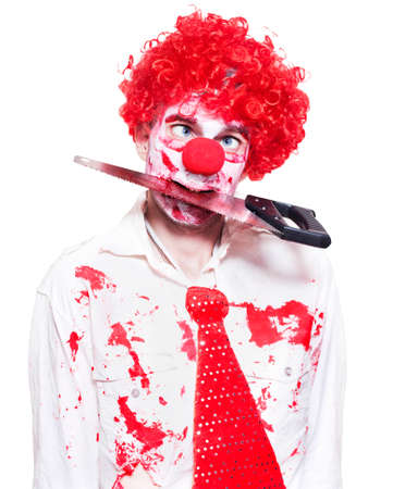 slasher: Isolated Creepy Clown Wearing Bright Red Wig Holding Bloody Saw In Mouth In A Depiction Of A Horror Slasher
