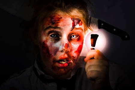 bloodied: Scary female zombie holding glowing lightbulb with exclamation mark in darkness. Halloween idea