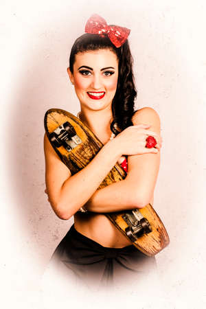 pinup girl: Vintage grunge photo of a beautiful brunette girl cuddling antique skateboard in 50s culture style. Skate love