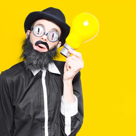 nerdy: Inspired Marketing Businessman Wearing Humorous Glasses And Fake Beard Holding Massive Light Bulb In A Depiction Of A Big Idea Stock Photo