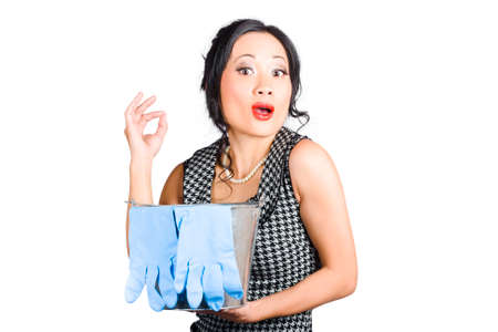 housemaid: Pretty asian lady holding housework pale with blue rubber gloves giving ok gesture. Clean inspection pass