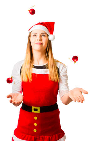 Cutout concept photo on a person in santa costume handling a fast paced christmas schedule while juggling red bulbuls. Catching the quick christmas rush
