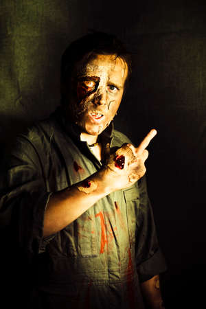 fingering: A walking dead zombie with decaying and rotting flesh gives a fingers up sign marking or singling out a person for their demise in a death threat concept
