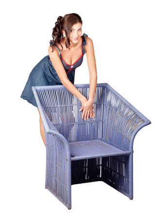 cane chair: Beautiful pin up woman with brown hair leaning on old cane chair. Fashion model Stock Photo