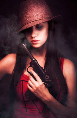 mobster: Sexy woman mobster with her hat pulled low over her eyes toting a large handgun in a dark shadowed portrait of criminal underworld figure