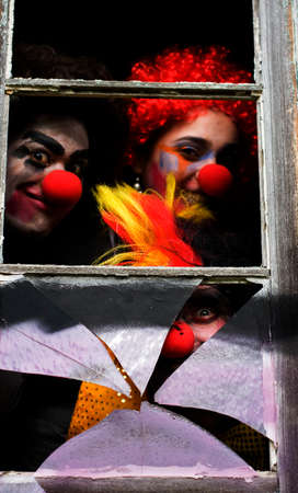 clowning: Dark Carnival Clowns Looking Sinister And Scary Peer Through A Haunted House Window At A Chilling Halloween Party Stock Photo