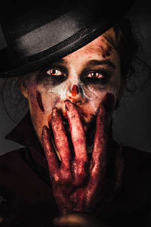 grisly: Dark frightening face of fear. Zombie holding severed hand to shocked face when killing the night with fright Stock Photo