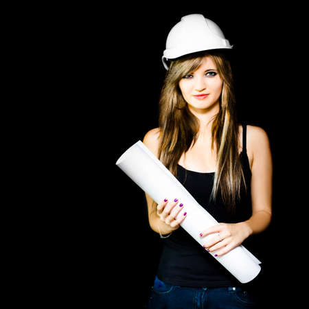 property development: Happy smiling graduate engineer in hardhat holding construction design plans in a property development and housing construction conceptual on dark background