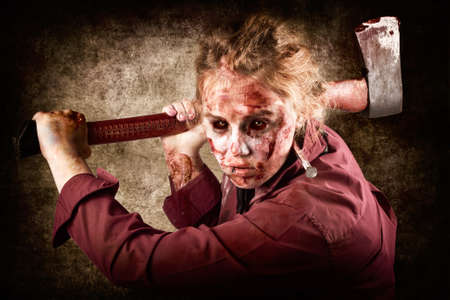 vindictive: Frightful portrait of a grunge zombie holding rusty old axe when chopping up Halloween victims of horror Stock Photo