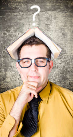quandary: Educated businessman thinking with information booklet on head when on a quest to answer question