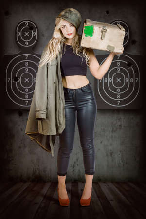 martial law: Propaganda style military portrait of a bomb shell blond army pinup girl carrying box of bullets at army shooting range with body target practice background. Bullet proof