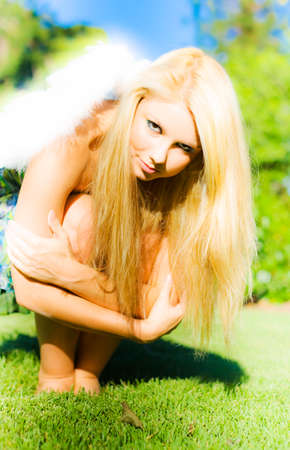 fallen: Pretty young blonde woman with feathery angel wings crouched down in the grass hugging her knees in a fallen angel concept