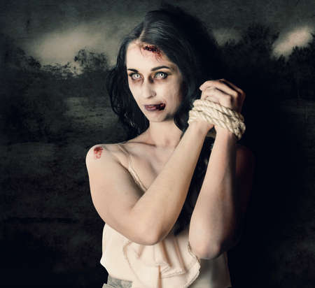 woman tied: Dark horror scene of an evil zombie woman with hands bound and tied, haunted grunge landscape background