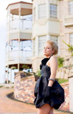 elegantly: Living The High Life A Wealthy Woman Stands Elegantly Dressed In Front Of Her Luxurious House