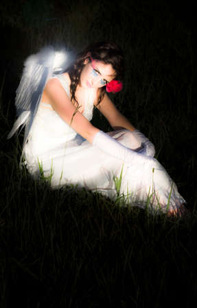 unearthly: Magical And Glowing Enchanted Angel Resting On A Grassy Meadow At Night With Her Wings Illuminating The Dark Scene In A Supernatural And Mystical Concept