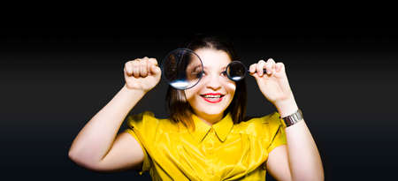 minutiae: An attractive young professional woman analyst holds up two different sized magnifying glasses as she delves and searches for statistics in a business competition analysis concept