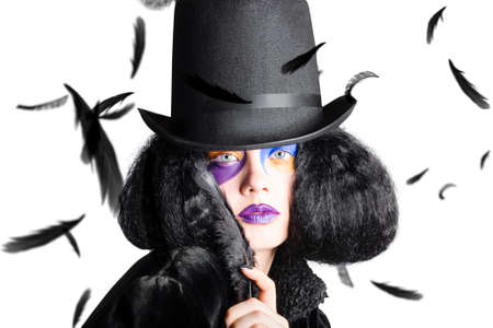 falling feather: Young vogue woman with colorful decorated face wearing black hat and costume in a cloud of black feathers Stock Photo