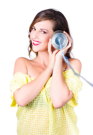 tin can telephone: Beautiful young woman with tin can telephone to ear, listening concept on white background. Stock Photo