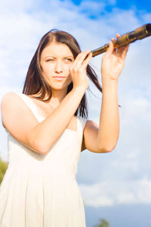 olden day: Attractive And Cute Visionary Woman With Spy Telescope Or Monocular Looking Out To Sea The Distant Horizon In Image Of Vision Visualization And Apparition Stock Photo