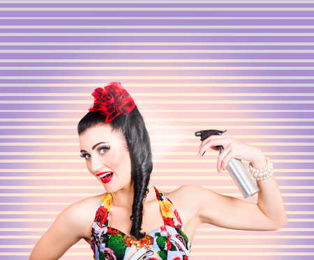 hair product: Funny portrait of a young pinup woman, spraying rolled brunette hairstyle with hair spray in a depiction of styling a hold with hair product Stock Photo