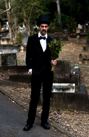 grieving: Morbidity Is The Deportment Of A Funeral Attendee Man Dressed In All Black As He Stands Holding Dead Flowers At A Cemetery Stock Photo
