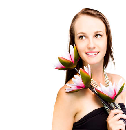 Elegant sophisticated woman in a black strapless dress and glittering necklace holding three exotic flowers over her shoulder looks back up into the frame